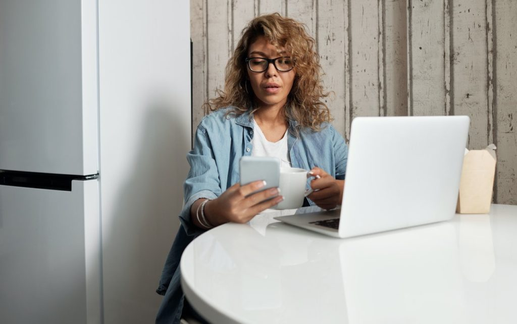 woman using smartphone and laptop